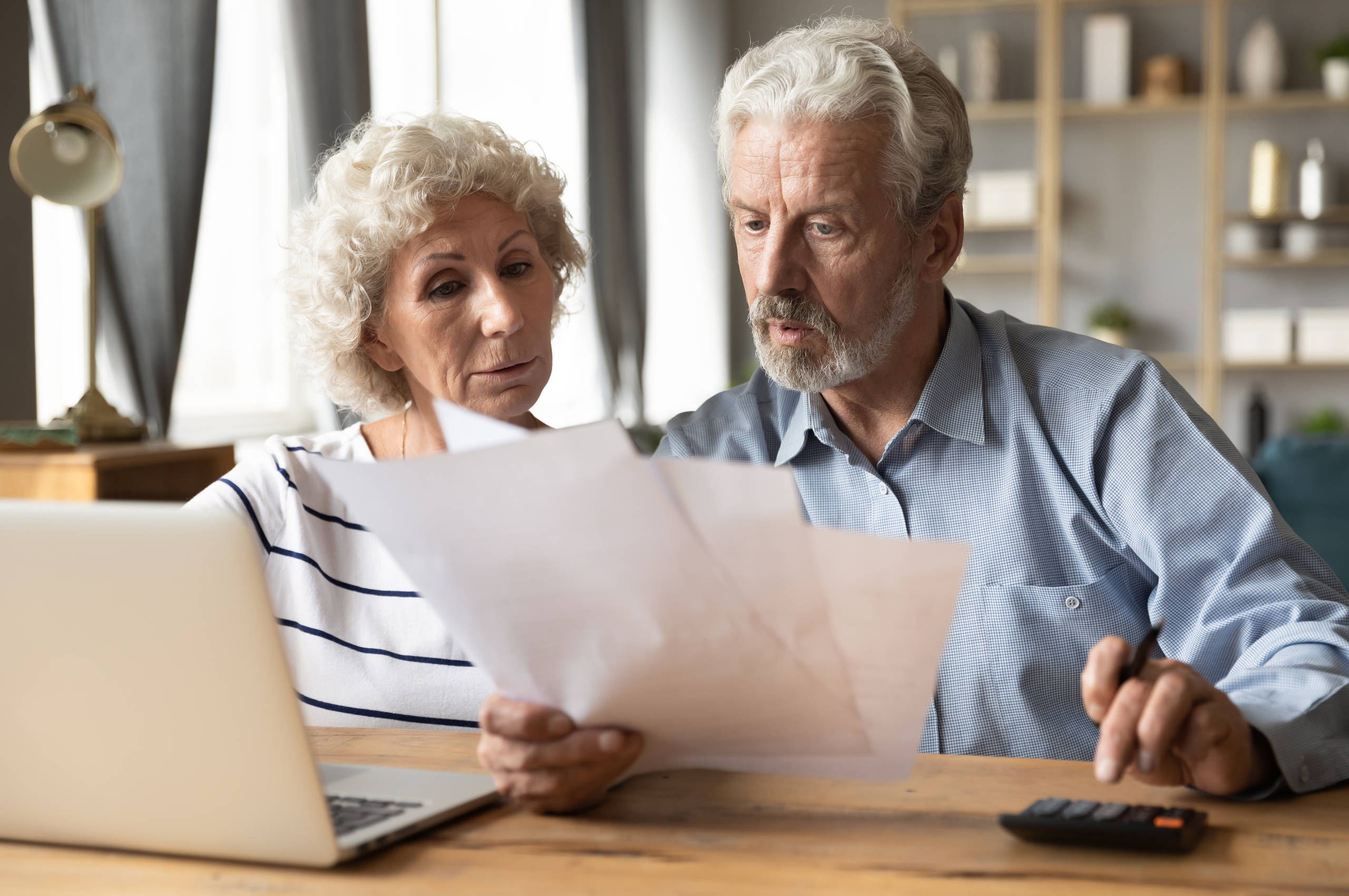 older couple looking serious reading financial documents and using calculator