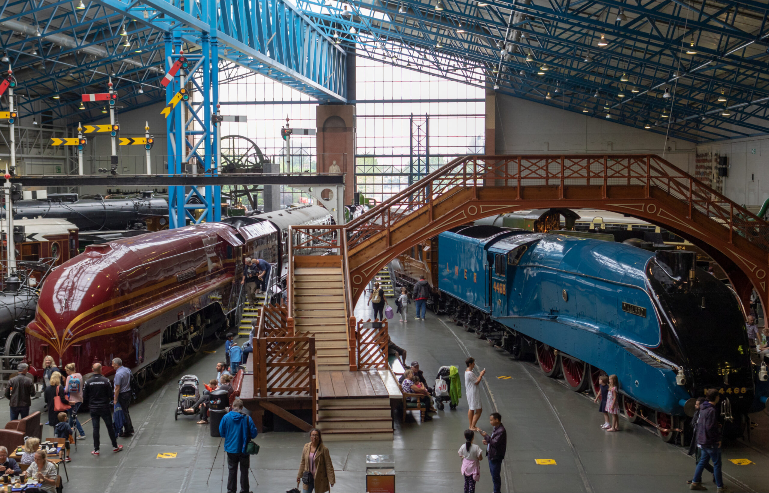 the inside of the National Railway Museum in York, with two trains either side of a set of wooden stairs
