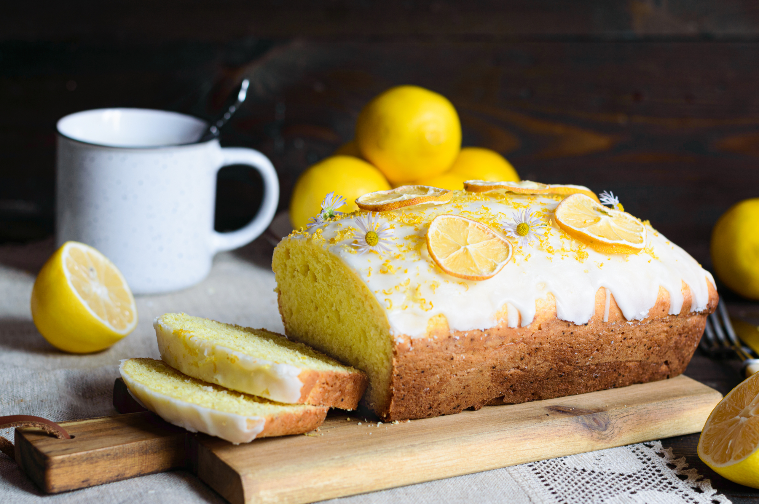 a lemon drizzle cake on a wooden chopping board