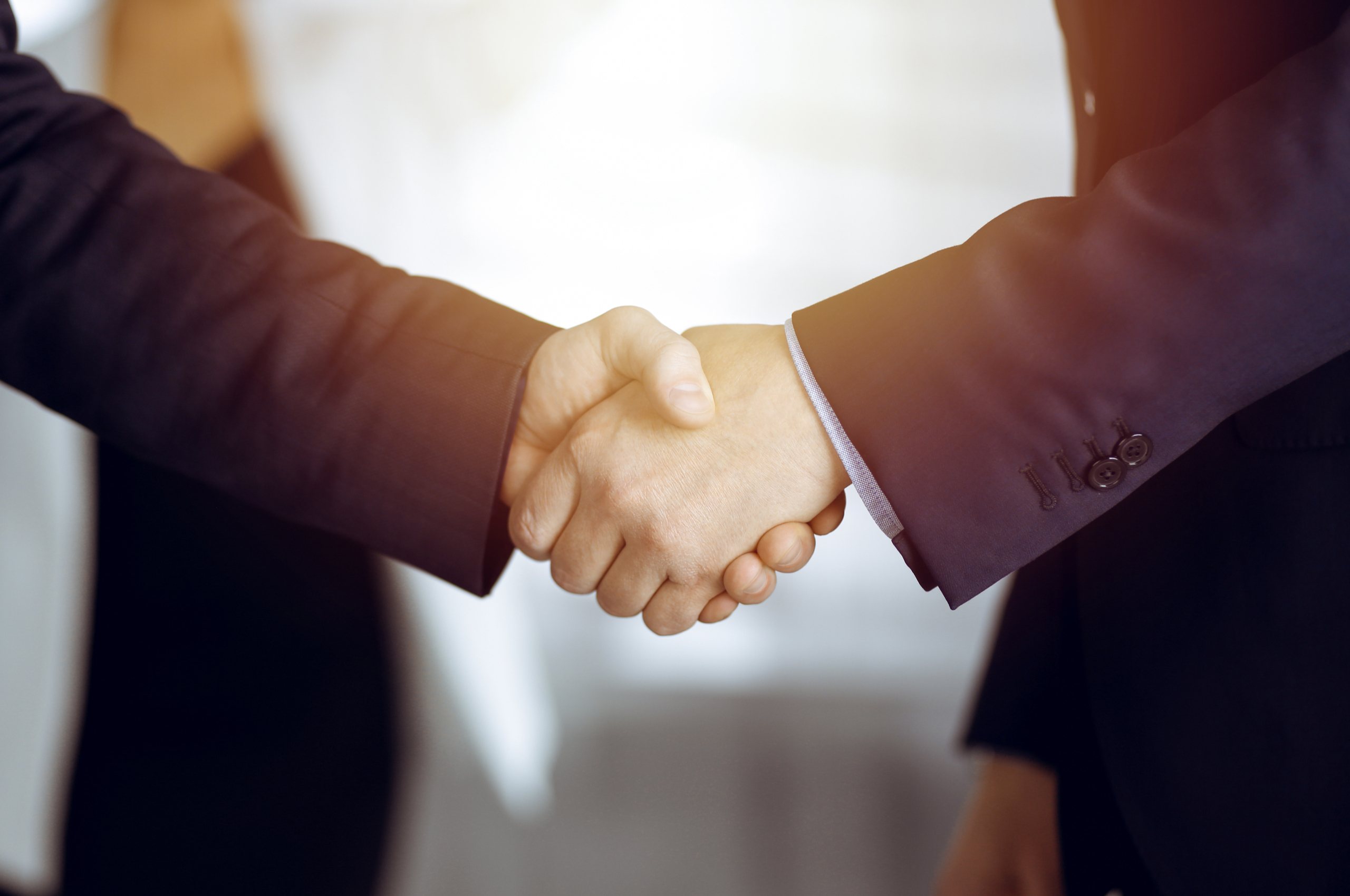 close up of a handshake by two people wearing suits